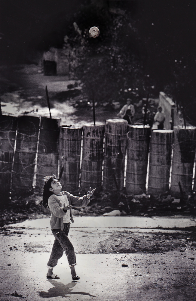 Palestinian Girl plays ball with backdrop of Israeli barricade : Jenin : West Bank