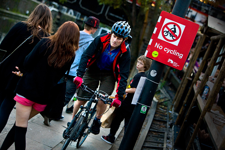 Cyclist On The Tow Path Pushing Through Pedestrians : Camden Lock : London